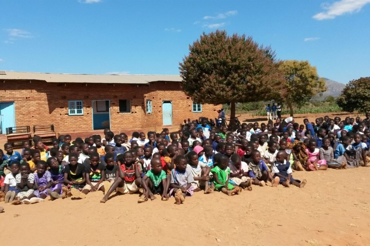 The whole school sitting outside newly painted school building